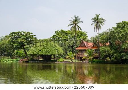 Thai style, Teakwood home in garden near river.