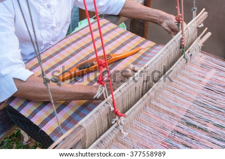 Thai style traditional hand-weaving loom being used to make cloth - stock photo