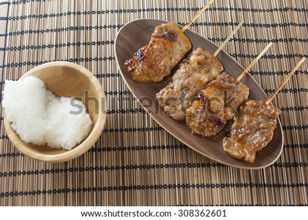 Thai-styled grilled pork and sticky rice on the mat. It's among most popular street foods in Thailand.  - stock photo