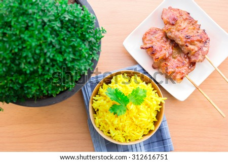 Thai-styled grilled pork. It's among most popular street foods in Thailand. With yellow rice eaten together. - stock photo