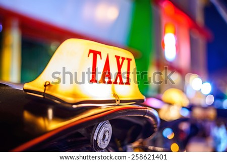Thai Taxi (Tuk Tuk) sign with defocused lights blur , Chiang Mai, Thailand. - stock photo
