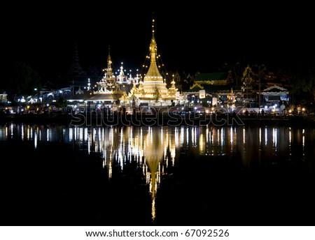 thai temple and reflection in the water at night