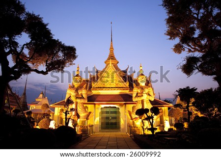 Thai temple with a golden glow and guarded by two huge statues. Shot with a view of blue evening sky in Bangkok, Thailand - stock photo
