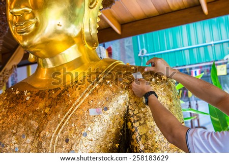 Thai tradition cover statue of Buddha with gold leaf and Hands were gilded  - stock photo