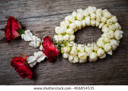 Thai Traditional garland made from Roses and jasmine on Wood table - stock photo