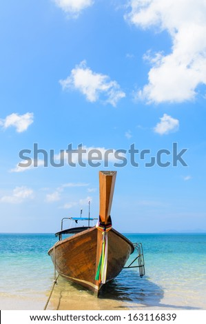 Thai Traditional longtail boat in the beach with blue sky background