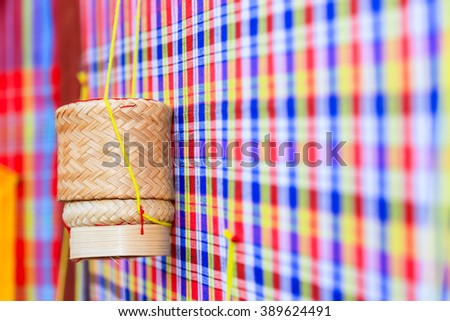 Thai traditional rice box called Kratib, wicker container made of bamboo for packing sticky rice, traditional wale textile loincloth, PAKAOMA or Kamar, common in culture of Isan, Thailand and Laos - stock photo