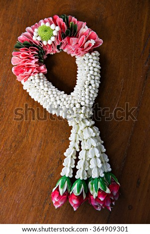 Thai Traditional Style of garland made from Roses and jasmine isolated on Wood background - stock photo