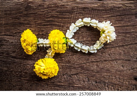 "Thai Traditional Worship Jasmine and Yellow Marigold Garland for Pay homage to the Buddha or for Blessing. Called ""Ma-Lai"" in Thai. / Wood Table Background and Textured. - stock photo"