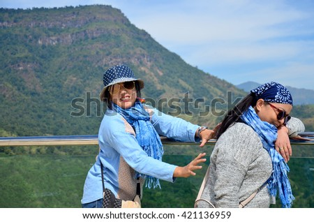 Thai woman and old women playing and portrait with view of Khao Kho mountain near Wat Pha Sorn Kaew at Khao Kor, Phetchabun, in north-central Thailand - stock photo