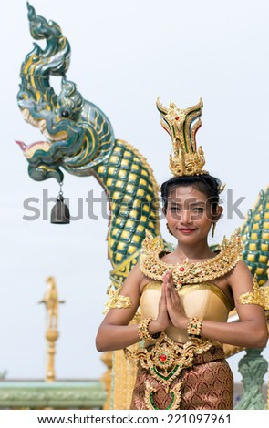 Thai woman in traditional costume with Buddhist greeting - stock photo