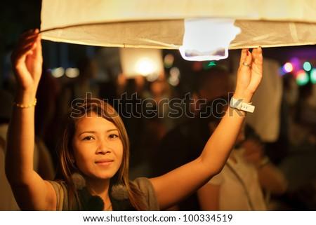 thai woman launching fire lantern during Loi Krathong Buddhist festival in Chiang Mai, thailand - stock photo