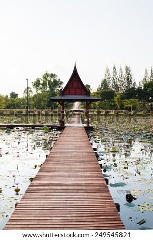Thai wood lake pavilion cottage and wooden bridge around with lotus flower and green leaf