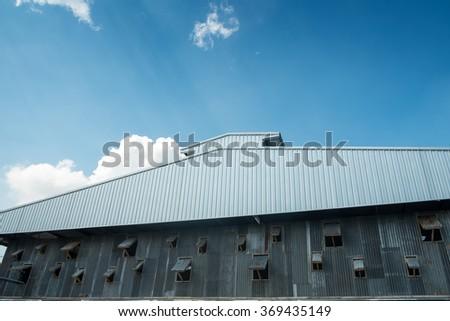 Thai zinc barn against clear blue sky and sun-rays - stock photo