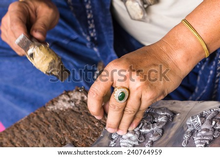 THAILAND - AUGUST 10:A carvers using a tool on a silver plate to carve on August 10, 2013 in Chiangmai,Thailand