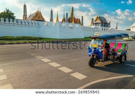 THAILAND, BANGKOK - NOVEMBER 8, 2014: Tuk tuk on the background of Bangkok's Grand Palace Complex and Wat Phra Kaew, one of Bangkok's tourist attractions, Bangkok, Thailand - stock photo