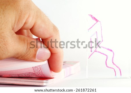Thailand banknotes and man hand during counting banknote action in the scene appear the hand drawing house shape on clear acrylic surface represent the mortgage concept idea. - stock photo