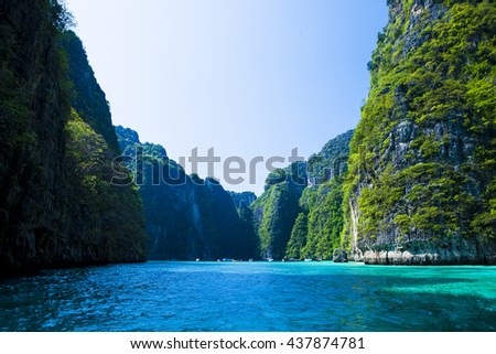 Thailand beach seascape with ring of steep limestone hills and traditional bright longtail boats parking, Maya Bay, Ko Phi Phi Lee island, Phi Phi archipelago, part of Krabi Province, Andaman Sea - stock photo