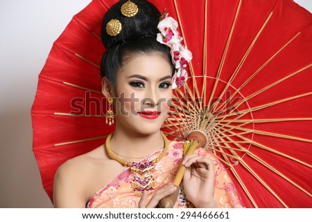 Thailand beautiful woman wearing a red umbrella.