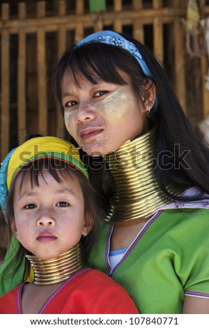 Thailand, Chiang Mai, Karen Long Neck hill tribe village (Baan Tong Lhoung), Long Neck woman with her child in traditional costumes. Women put brass rings on their neck when they are 5 or 6 years old