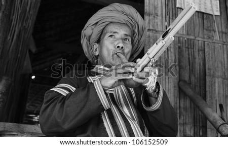 Thailand, Chiang Mai, Karen Long Neck hill tribe village (Kayan Lahwi), Karen man in traditional costumes playing a flute - stock photo