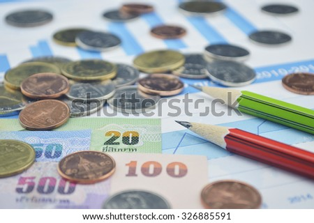 Thailand coins, banknotes and pencils on business graph, accounting background - stock photo