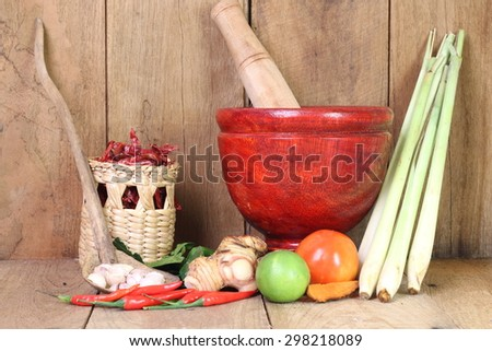 Thailand Food Ingredients: lemon, lime, galangal, ginger , tomato, mango leaves the dungeon, garlic on a wooden floor. - stock photo