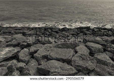 Thailand/ June 2015. Rocky shore. The rocks were placed on the edge of the ocean to prevent land erosion by the water force. The photo is in Black and White. - stock photo