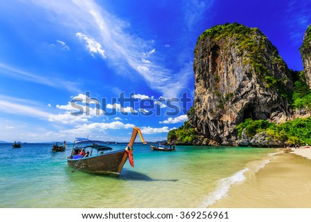 Thailand, Krabi. Long tail boat on tropical beach with limestone rock.