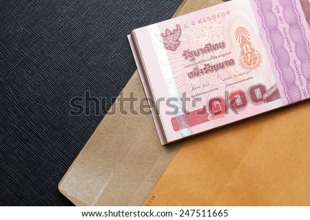 Thailand one hundred baht banknotes put on the brown color paper envelope represent the Thai financial and monetary  related.