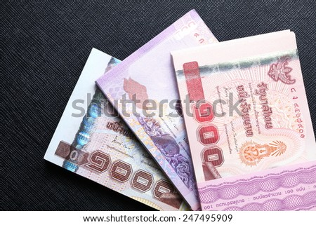 Thailand one thousand baht five hundred baht and one hundred baht banknotes put on the black color leather surface background represent the Thai financial and monetary  related. - stock photo