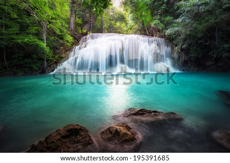 Thailand outdoor photography of waterfall in rain jungle forest. Trees, foliage and clear water of mountain river  - stock photo