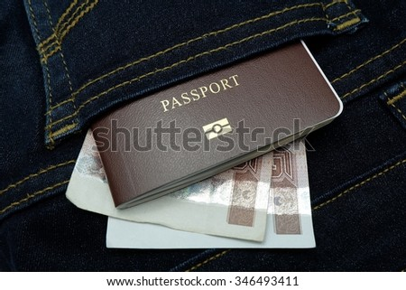 Thailand passport and money in back pocket jean pants.