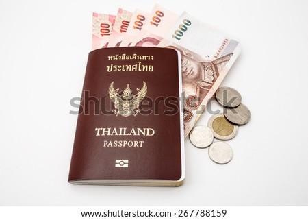 Thailand passport and Thai money on white background - stock photo