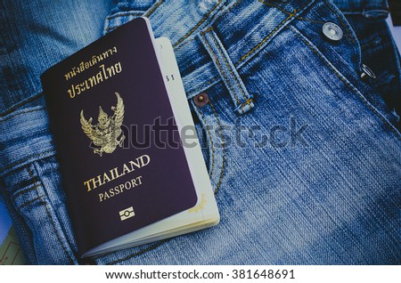 Thailand passport , on  jeans background.Holiday Travel.close up of an Thailand passport  - stock photo