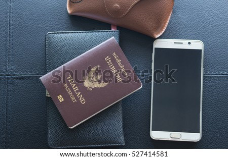 Thailand passport, smartphone, notebook and glasses. Preparing to travel abroad