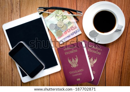 Thailand Passport with currency , Coffee and Cell Phone on a Wood Background. - stock photo