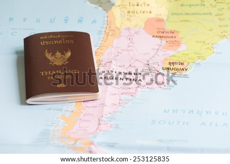 Thailand Passports on a map of the Argentina. - stock photo
