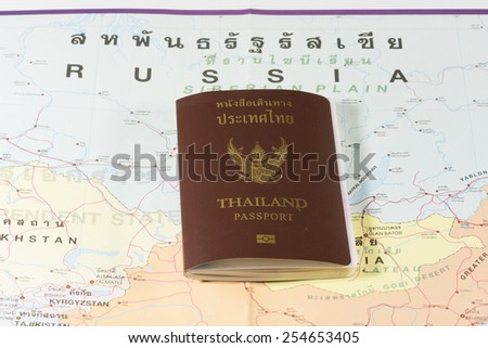 Thailand Passports on a map of the Russia and Kyrgyzstan. - stock photo