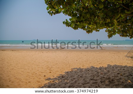 Thailand. Rayong. Ocean view with yellow sand, blue water, waves and palm tree