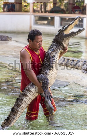 """THAILAND, SAMUT PRAKAN - December 27,2015: An unidentified zoo keeper embrace crocodile as part of """"Show of crocodiles"""" at Samut Prakan Crocodile Farm and Zoo. - stock photo"""