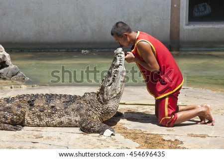 """Thailand, Samut Prakan - July, 18, 2016 : Unidentified zoo keeper kiss the crocodile as part of """"Show of crocodiles"""" at Samut Prakan Crocodile Farm and Zoo. - stock photo"""