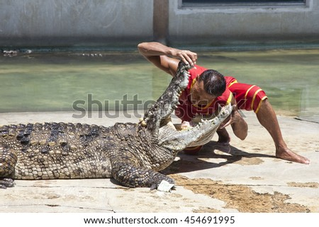 """Thailand, Samut Prakan - July, 18, 2016 : Unidentified zoo keeper puts a head in a mouth of the crocodile as part of """"Show of crocodiles"""" at Samut Prakan Crocodile Farm and Zoo. - stock photo"""