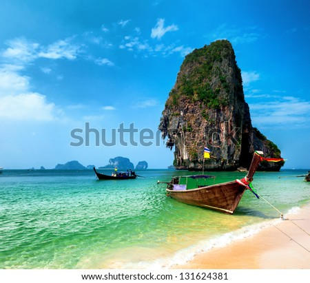 Thailand sandy beach and traditional thai wooden boat - stock photo