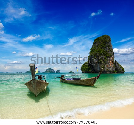 Thailand travel holidays background. Long tail boats on summer tropical sea beach (Pranang beach), Krabi, Thailand