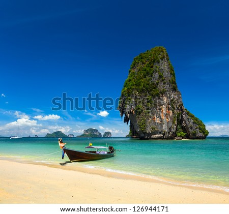 Thailand tropical vacation concept background - Long tail boat on tropical beach with limestone rock, Krabi, Thailand