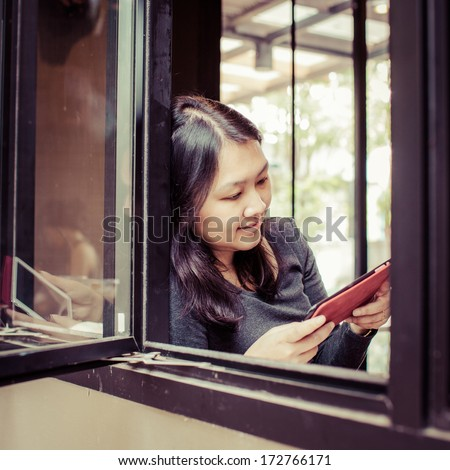 Thailand woman using tablet computer touchscreen ipad in cafe,process color - stock photo