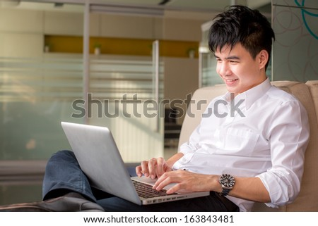 Thailand Young man relaxing on the sofa with a laptop - stock photo