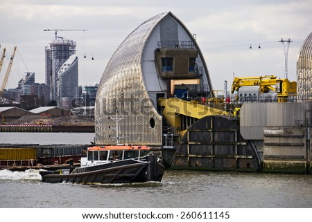 Thames Barrier; Tug boat passing through The Thames Barrier  - stock photo