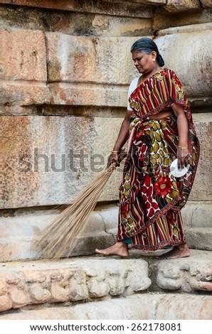THANJAVUR, INDIA - FEBRUARY 14: An unidentified Indian woman in national dress carries sweeping a broom at Brihadishwara Temple. India, Tamil Nadu, Thanjavur. February 14, 2013. - stock photo